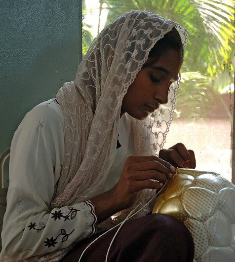 photo of woman hand-stitching a soccer ball