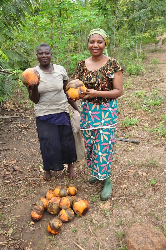 photo of two women holding large fruits